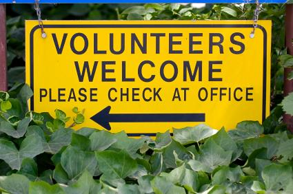 "Sign which reads ""Volunteers welcome. Please check at office."""